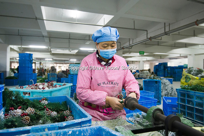 November 28, 2015, Yiwu China - A male worker makes Christmas trees inside Sinte An Christmas tree factory. The factory produces a variety of artificial trees for global export throughout the year.Photo by Dave Tacon / Sinopix
