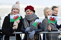 04/02/2020 - Members of the public hold Welsh flags while waiting for the arrival of the Duke and Duchess of Cambridge, where they will visit the RNLI Mumbles Lifeboat Station, near Swansea in south Wales. Photo Credit: ALPR/AdMedia