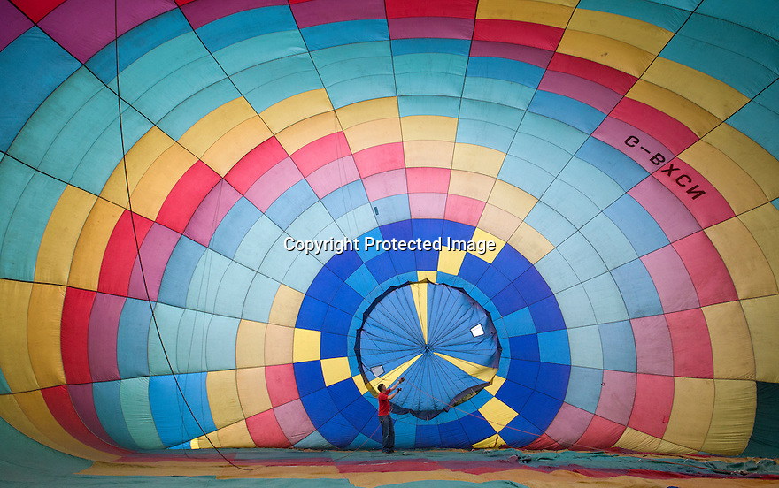 07/06/16<br /> <br /> Robin Macey checks the inside of the balloon as it is inflated.<br /> <br /> After weeks of rain the Nottingham and Derby Hot Air Balloon Club finally get to launch their three hot air balloons from Allestree Park, Derby.