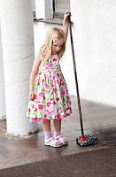 Young polish girl age 4 in flowered dress resting from mopping front porch of her home. Zawady Central Poland