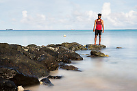 """Dencus Tanalua, 24, a carpenter, stands near the shoreline in central Funafuti, the capital of the small Pacific nation of Tuvalu. Land poor micro-states in the region are some of the most vulnerable to climate change impacts. This has driven many to flee their homelands, in fear of the potential environmental catastophes their countries are vulnerable to, and also in search of higher incomes through better job opportunities provided by other larger countries. It is estimated nearly 20% of Tuvalu's population have left and reside in other countries such as New Zealand and Australia. Young adults are the most likely to leave, with the older generation most likely to stay. A recent report by The Australian National University estimates by 2050, """"47% of Tuvaluan adults (4,900 people)...will want to migrate but [will] be unable to do so"""", with limiting factors being financial and available places on migration programs to other countries. Funafuti, Tuvalu. March, 2019."""