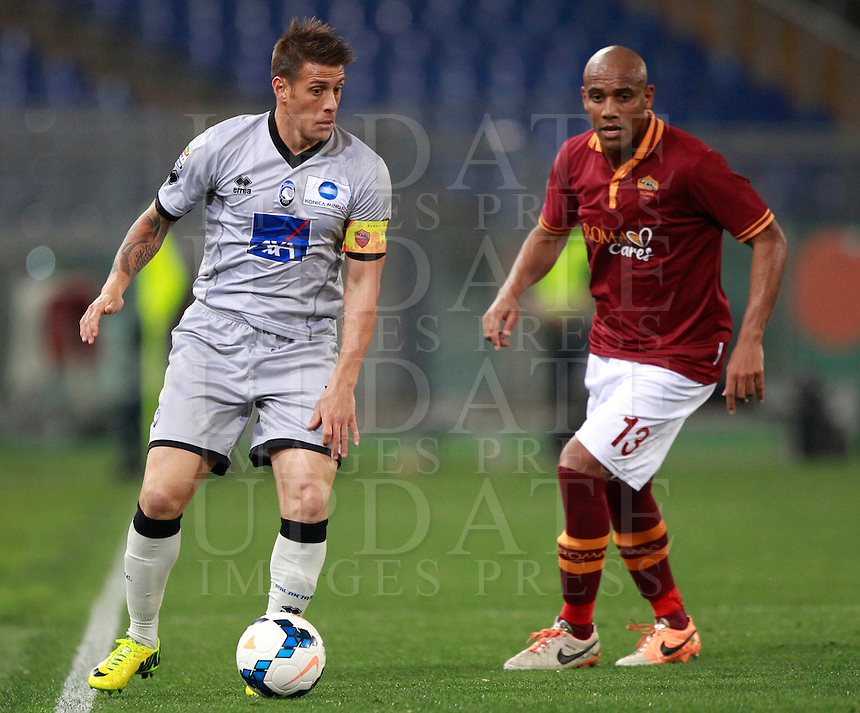 Calcio, Serie A: Roma vs Atalanta. Roma, stadio Olimpico, 12 aprile 2014.<br /> Atalanta forward German Gustavo Denis, of Argentina, is challenged by AS Roma defender Maicon, of Brazil, right, during the Italian Serie A football match between AS Roma and Atalanta at Rome's Olympic stadium, 12 April 2014.<br /> UPDATE IMAGES PRESS/Isabella Bonotto