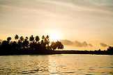 INDONESIA, Mentawai Islands, Kandui Resort, silhouette of an island with palm trees at dusk, Karangmajat