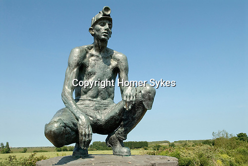 Bettshanger Kent UK. Statue of a Kent miner with miners hat and lamp. Fowlmead Country Park, which was where the spoil heap from the mine was situated. Where cutting is, was three times that height.
