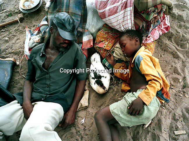 A father and son resting in Chakuelane, a transit camp for victims of the severe flooding in Mozambique in february-March 2000. About 80.000 people gathered here to get shelter and food from international Aid agencies..©Per-Anders Pettersson/iAfrika Photos