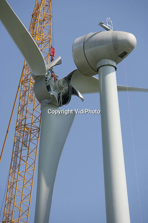 Foto: VidiPhoto..ECHTELD - De Duitse uitvoerder Enercon plaatst woensdag een rotor op een enorme windmolen langs de A15. Op die plek verreist op dit moment Windpark Echteld, met vier turbines van 78 meter hoog en een vermogen van 2 megawatt. Daarmee behoren ze tot de grootste windturbines van Nederland. Opdrachtgever is WEOM/NUON. De bouwkosten bedragen 10-12 miljoen euro.