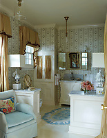 The ensuite bathroom is decorated in cool blue and white with neutral curtains.