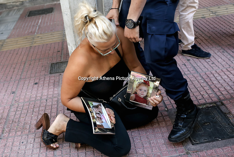 Pictured: A relative of two of the victims, Theodosios Katifes and five year old Sevasti Katife collapses on the ground as Tharsivoulos Lykourezos, the captain of the speedboat arrives at Piraeus Court.<br /> Re: Tharsivoulos Lykourezos, the captain of a speedboat that collided with a tourist boat off the Greek island of Aegina, leaving four people dead, has appeared in court and was given until Friday to prepare his defense.<br /> Relatives of the victims shouted insults and were held back by police as the 77-year-old arrived at the courthouse in Greece's main port city of Piraeus.<br /> The speedboat called Duente collided Tuesday with a tourist boat called Antonia carrying more than 20 people from the island to a beach on a nearby islet. The dead included a 5-year-old girl and her father. Authorities initially said the child was about 9.<br /> The health ministry says 16 people in all were hurt, with five requiring hospital treatment. Two suffered serious injuries, including a woman whose leg was partially severed.