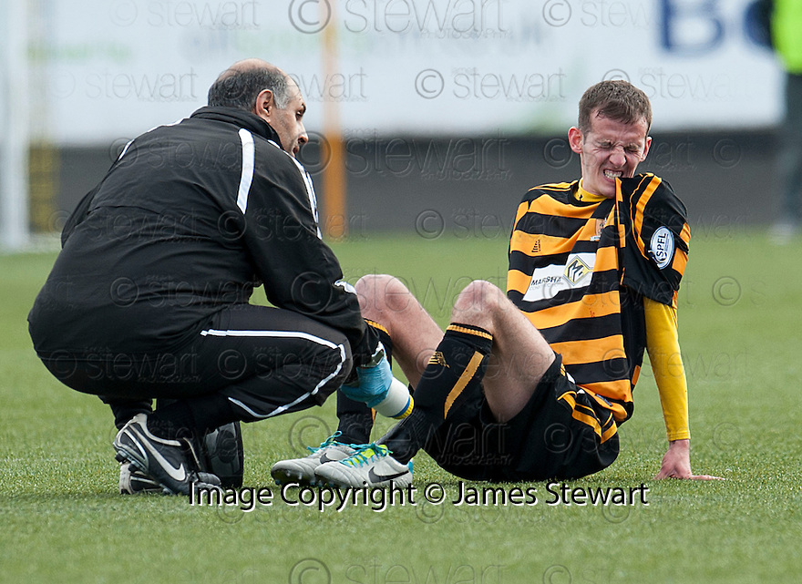 Alloa's James Creaney bits his shirt as the pain of his foot injury sets in.