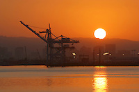 The cranes at the Port of Oakland stand ready as the sun rises above the city skyline. The Port of Oakland is the fourth largest shipping terminal in the United States behind Long Beach, Los Angeles, and Newark.