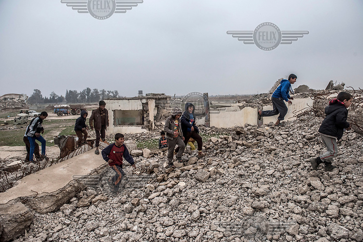 Children play in the rubble of a destroyed building outside Hamam Alil displaced peoples' camp to the south of Mosul.