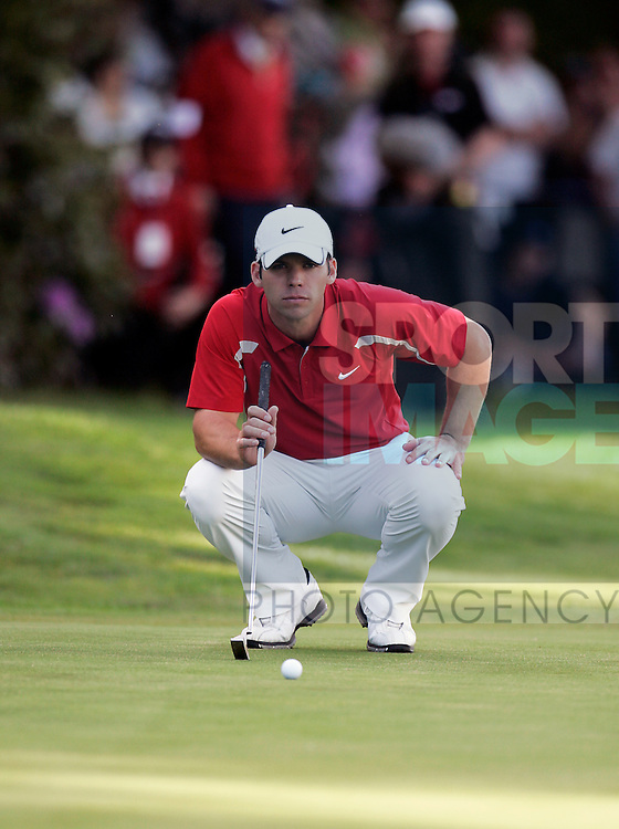 Paul Casey of England lines up a putt on the 18th green