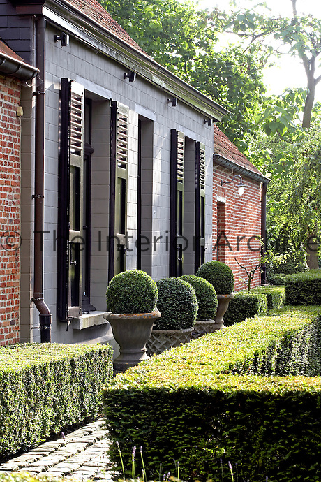 Brick paths and box hedging create a formal yet tranquil garden on one side of the farmhouse