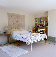 A hand-stitched wall hanging graces the wall behind this simple wrought-iron bed
