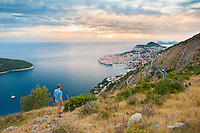 Dubrovnik Old Town sunrise, a tourist admiring the view from Zarkovica Hill, Dalmatian Coast, Croatia. This is a photo of a tourist admiring an elvated view of a Dubrovnik Old Town sunrise, taken from Zarkovica Hill. It shows Dubrovnik Old Town jutting out into the Adriatic Sea on the Dalmatian Coast in Croatia. By far the best views of Dubrovnik are from elevated points such as Zarkovica Hill, especially at sunrise.