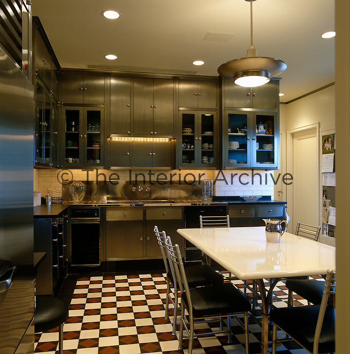 This well-designed contemporary kitchen/diner combines smart space-saving units and stainless steel equipment with a modern table and chairs