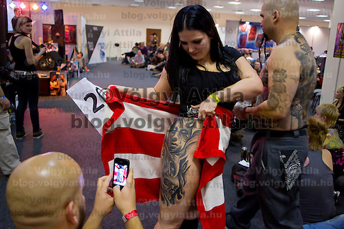 Participant shows off her tattoo during an international tattoo exhibition in Budapest, Hungary on February 26, 2012. ATTILA VOLGYI
