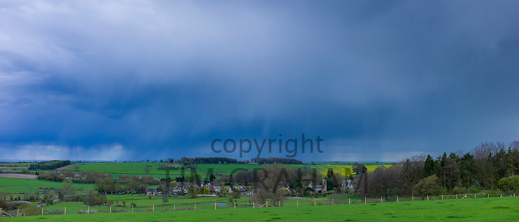 Storm clouds in cloud formation above Asthall Village in springtime in the Cotswolds, Oxfordshire, UK