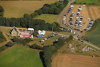 Cette vue aerienne montre la totalite de l'installation avec la chapelle, la scene mobile, les abris ainsi que les parking sur prairie et sur champs fraichement moissonne