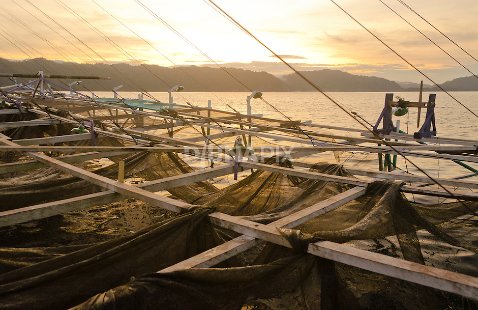 Sunset view from a the largest bagan fishing boat in the Kaimana area -- about 30x30 meters. Large nets scoop up large and small fish alike, resulting in a lot of unsaleable bycatch, and depleting the bait fish upon which larger fish and marine mammals depend.