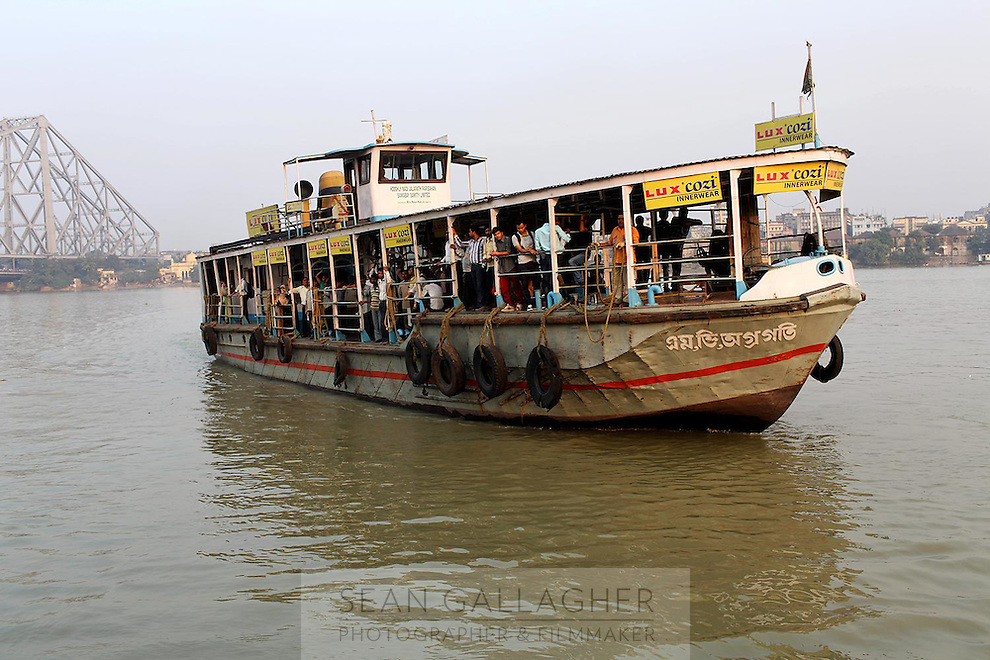 A passenger boat cruises along the Ganges River in Kolkata.<br />