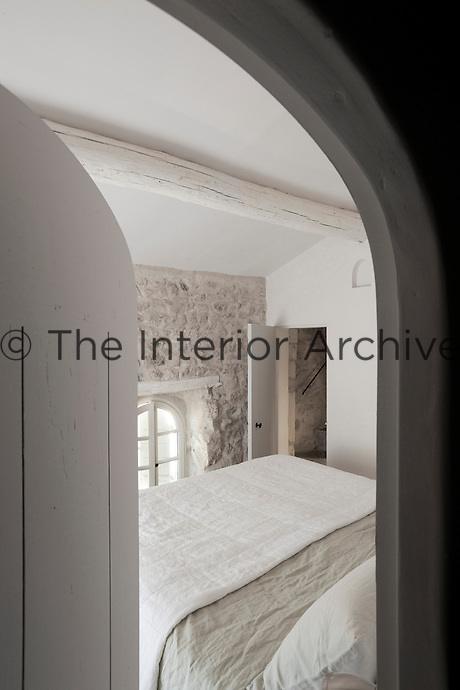 A large comfortable bed dominates this small bedroom glimpsed through the open door