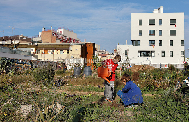 Children watering vegetables in El Hort Indignat, an urban allotment project in the El Poblenou district of Barcelona, Catalonia, Spain. The industrial neighbourhood fell into decline after the Industrial Revolution, and has recently been redeveloped, triggered by the Olympic Games of 1992, with old factories converted into apartment buildings and offices, resulting in a vibrant, young and artistic community. Picture by Manuel Cohen