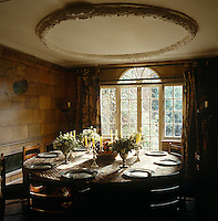 The dining room in this early Georgian house has walls in a trompe l'oeil brick with an original plaster ceiling decoration