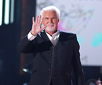 """20 March 2020 - Kenny Rogers, whose legendary music career spanned nearly six decades, has died at the age of 81. Rogers was inducted to the Country Music Hall of Fame in 2013."""" He had 24 No. 1 hits and through his career more than 50 million albums sold in the US alone. He was a six-time Country Music Awards winner and three-time Grammy Award winner. Some of his hits included """"Lady,"""" """"Lucille,"""" """"We've Got Tonight,"""" """"Islands In The Stream,"""" and """"Through the Years."""" His 1978 song """"The Gambler"""" inspired multiple TV movies, with Rogers as the main character. File Photo: June 9, 2004; Nashville, TN, USA; Singer KENNY ROGERS during CMT 100 Greatest Love Songs Telecast Taping held at Gaylord Entertainment Center. Mandatory Credit: Photo by Laura Farr/AdMedia"""