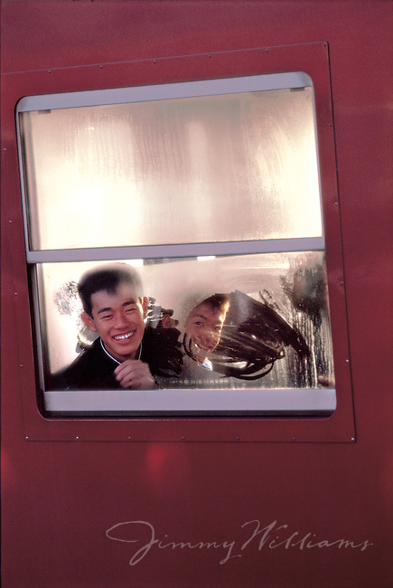 Two young Japanese boys smile through an area they wiped away on a frosted window