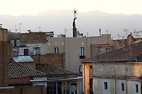 Rooftops of the old town or Casc Antic and Monument to the Ebro battle, made 1966 by Lluis M Saumells Panades and inaugurated by General Franco, with mountains behind, Tortosa, Tarragona, Spain. The sculpture is the Nationalist War Memorial commemorating the dead from the Spanish Civil War battles of 1938 and is in the Ebro River. Tortosa is an ancient town situated on the Ebro Delta which has a rich heritage dating from Roman times. Picture by Manuel Cohen