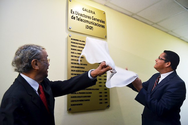 El presidente del Indotel, licenciado Gedeón Santos, acompañado del doctor Víctor Hidalgo Justo, develan una tarja con los nombres de los ex directores de la antigua Dirección General de Telecomunicaciones (DGT) en la Galería de Ex Presidentes del Indotel.