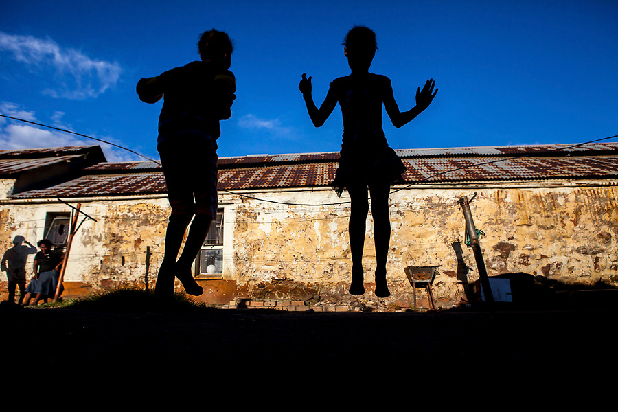 Children skip in an abandoned gold mine hostel where squatter families now reside outside of Johannesburg, South Africa.
