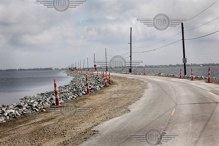 The heavily eroded road that leads to Isle de Jean Charles on the coast of Louisiana. Coastal erosion, due largely to damage from the oil and gas exploration and extraction in coastal marshlands, has left the landscape tattered and communities endangered by land loss.