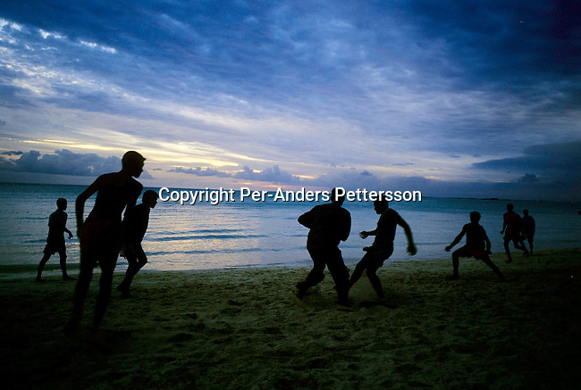 GRAND BAY, MAURITIUS - JULY 2 :  .Men play soccer on the beach as the sun sets on July 2, 2003, in Grand Bay on Mauritius. The island, located in the Indian Ocean, is a popular place for tourists with unspoiled beaches and nature. .(Per-Anders Pettersson/Getty Images)