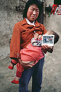 September, 1985. Shaanxi Province, China. A mother nursing her child in the area of Wuqi.