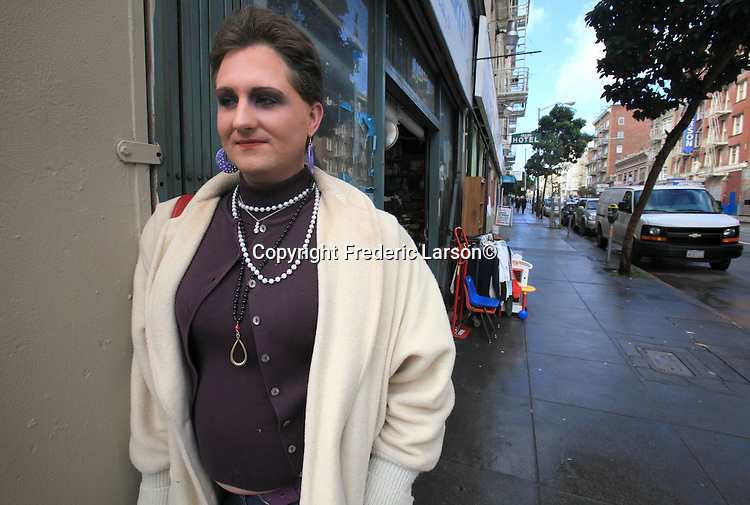 """""""Serenity""""  who just arrived in San Francisco from Oklahoma City poses for a photograph along a storefront window in the Tenderloin district of San Francisco, California."""