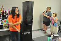 NWA Democrat-Gazette/MICHAEL WOODS &bull; @NWAMICHAELW<br /> Anna Huynh (left) gets ready to photograph Holly Davenport and her daughter Braylee, 8, from West Fork Friday August 7, 2015 at the photo booth during the Education Expo presented by the Fayetteville Chamber of Commerce at Cardinal Arena in Farmington.  The expo recognized staff members of the 6 school districts in Washington county with food, swag bags, door prizes and games.