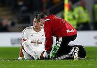 Franck Tabanou of Swansea City receives treatment for his injury during the Capital One Cup match between Hull City and Swansea City played at the Kingston Communications Stadium, Hull