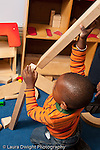 Education preschool 3-4 year olds block area boy building with long blocks putting one on top of another vertically
