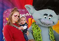 NWA Democrat-Gazette/DAVID GOTTSCHALK Patricia Myer holds her son Coy Fitts, 1, as they stand with Troll characters Friday, November 2, 2018, during First Friday/Toyland in downtown Bentonville. Hosted by Downtown Bentonville Inc., the event featured Walmart venders bringing out toys and lifesize characters to give out toys, promotional items and to interact with visitors.