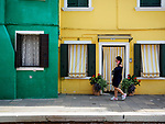 A woman in black walks with a pink cell phone in the colorful village of Burano, Italy.