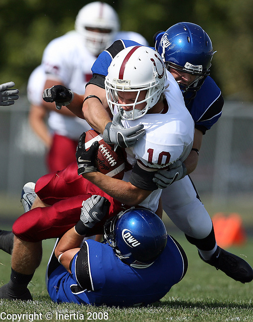 MITCHELL  - SEPTEMBER 27: David Chochon #10 of Hastings is brought down by Eric Adolph #4 top and Dane Carlson #29 of Dakota Wesleyan University in the first quarter Saturday afternoon at Joe Quintal Field in Mitchell. (photo by Dave Eggen/Inertia)