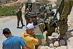Palestinian protesters prepare for the imminent detonation of a concussion grenade dropped amongst them at an Israeli army road block during a demonstration against Israel's controversial separation barrier in the West Bank town of Beit Jala near Bethlehem on 04/07/2010.