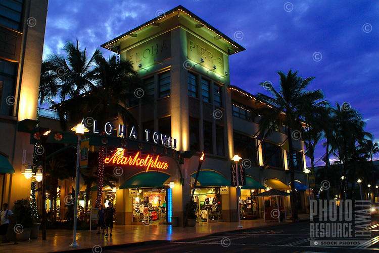A tropical evening in front of illuminated Aloha Tower Marketplace in downtown Honolulu.