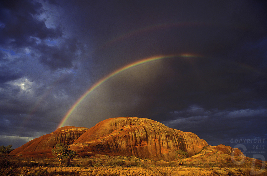 "A rare Rainbow over the Olgas, Northern Territory in Central Australia.<br /> It is believed that this is the first and only image ever taken with a rainbow over the Olgas until now. An award winning image published many times shot on Kodachrome film.<br /> it was also use on the Cover of ""Die letzten Nomaden"" in 2007 by<br /> ARAKI PUBLISHERS, Germany published the book Die letzten Nomaden - The last Nomads of Australia by international Author William J.Peasley the book has been published numerous times in Australia and the Documentary Film received in 1997 a Gold medal at the New York Film Festival. Cover Photo by Gunther Deichmann, a well known and multi awarded image of the Olgas with a Rainbow taken in the Northern Territory of the Australian outback."