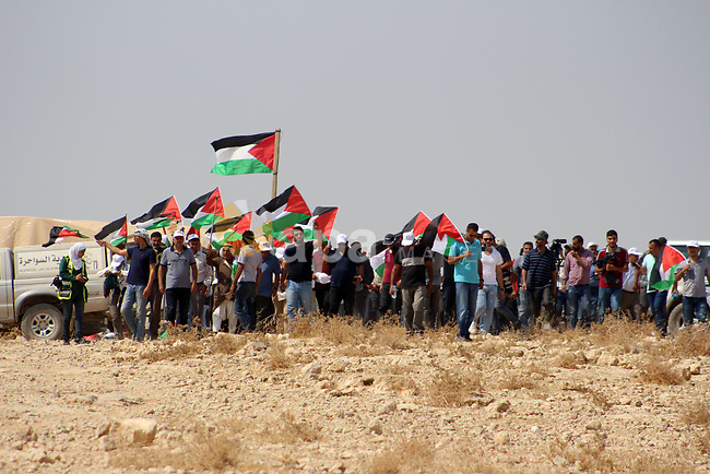 Palestinian activists and land owners hold Palestinian flags and shout during a protest against a new settlement in the West Bank village of Sawahra, east of Jerusalem, 20 September 2019. Photo by Mosab Shawer