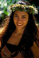 Young smiling Hawaiian hula dancer in a park in Honolulu on Oahu