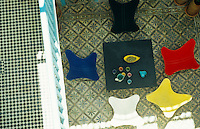 Looking down onto a group of colourful Betoia chairs around a coffee table in the tiled interior courtyard