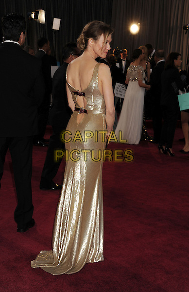 Renee Zellweger (wearing Carolina Herrera).85th Annual Academy Awards held at the Dolby Theatre at Hollywood & Highland Center, Hollywood, California, USA..February 24th, 2013.oscars full length gold sleeveless dress bracelet backless straps red bows profile back behind rear looking over shoulder .CAP/ROT/TM.©Tony Michaels/Roth Stock/Capital Pictures